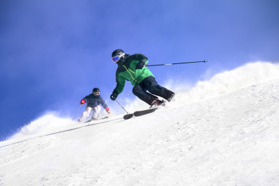 Two Skiers skiing downhill in high mountains and sunny day
